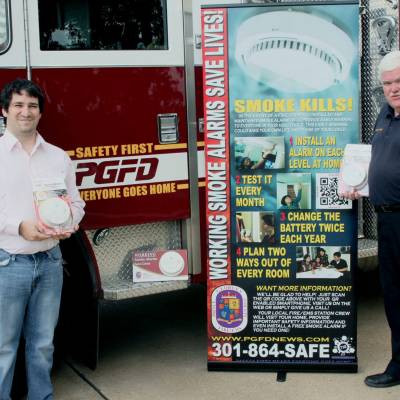 PIO Brady is pictured with reporter promoting smoke alarm safety